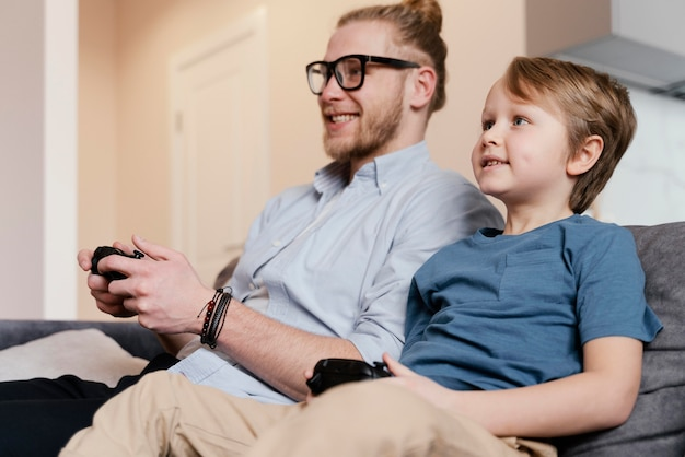 ミディアムショットの子供と父親が遊んでいます
