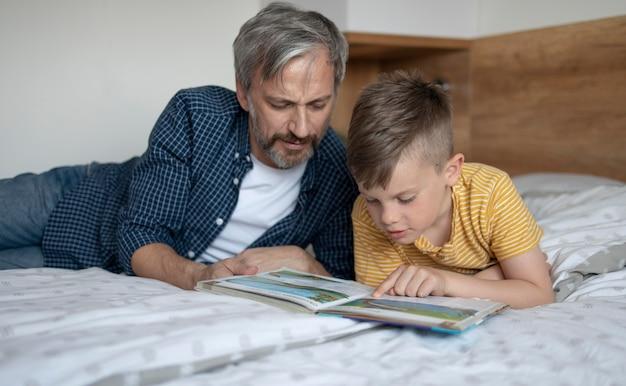 ミディアムショットの子供と父親の読書