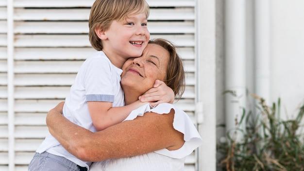 ミディアムショットの子供とおばあちゃんが抱き締める