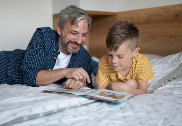 ミディアムショットの子供と男性の読書