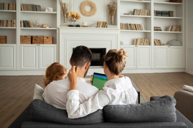 Ребенок среднего кадра и родители с устройством