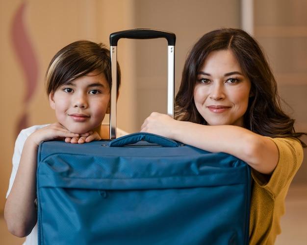 Средний выстрел ребенок и женщина с багажом