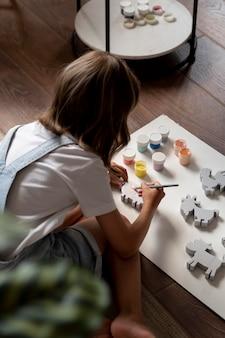 Ребенок среднего роста занимается творчеством дома