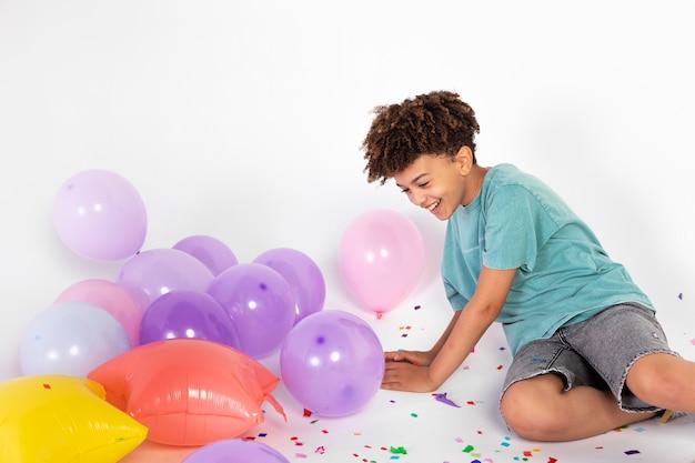 Ragazzo di tiro medio che festeggia con i palloncini