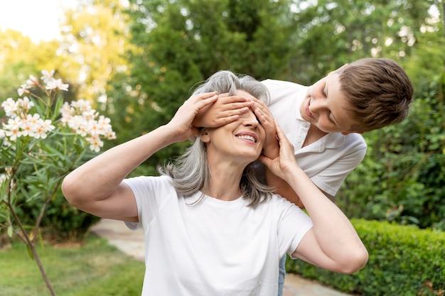 祖母の目を覆うミディアムショットの子供
