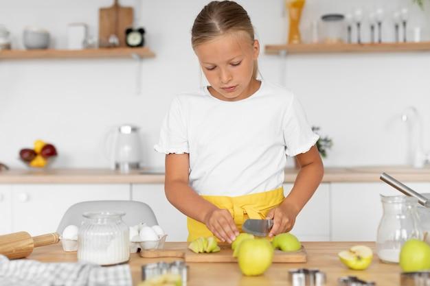 ミディアムショットの子供がリンゴを切る