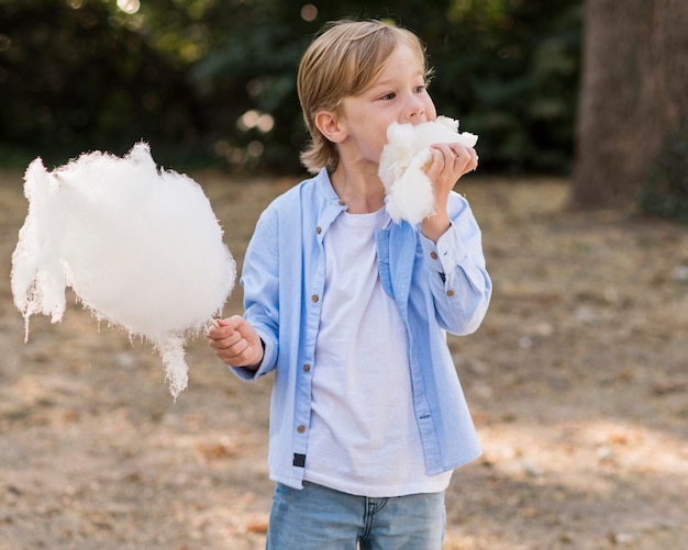 Medium shot kid eating cotton candy