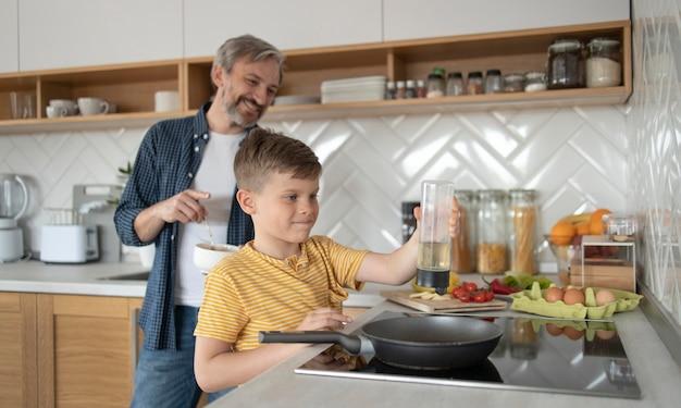 Ragazzo e padre di tiro medio che cucinano