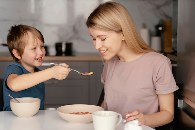 Средний снимок ребенка, обнимающего мать