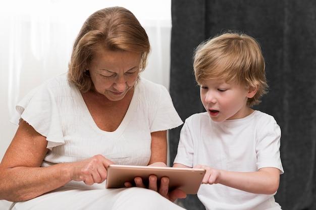 Ragazzo e nonna a tiro medio con tablet