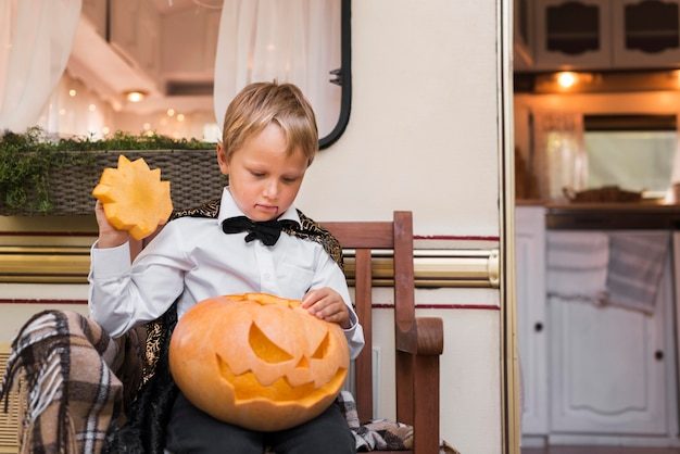 Medium shot kid holding carved pumpkin