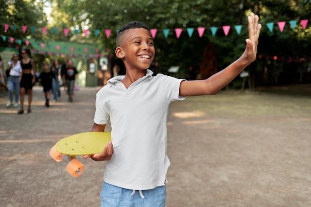 Medium shot kid holding penny board