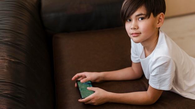 Средний выстрел ребенок держит смартфон