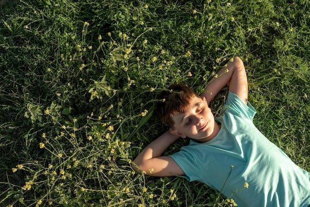 Ragazzo del colpo medio che pone sull'erba
