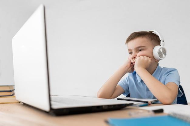 Ragazzo del colpo medio che esamina il computer portatile