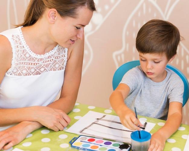 テーブルでミディアムショットの子供絵画