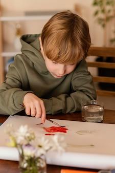 赤で絵を描くミディアムショットの子供