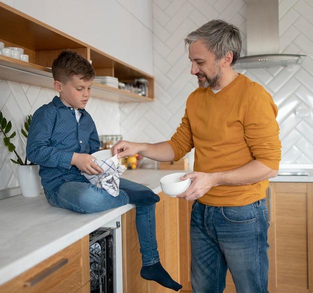 Ragazzo e genitore di tiro medio in cucina