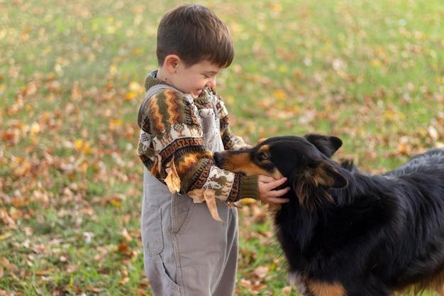 ミディアムショットの子供が犬を撫でる