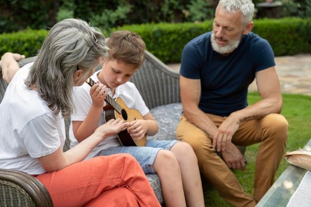 조부모를 위해 음악을 연주하는 중간 샷 아이