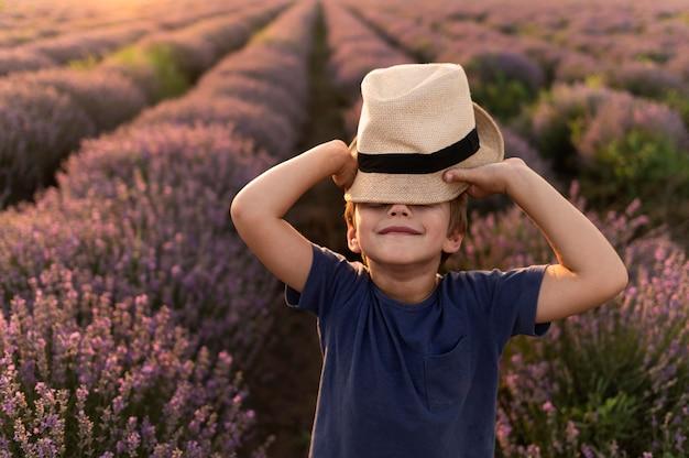 ミディアムショットの子供が帽子でポーズ