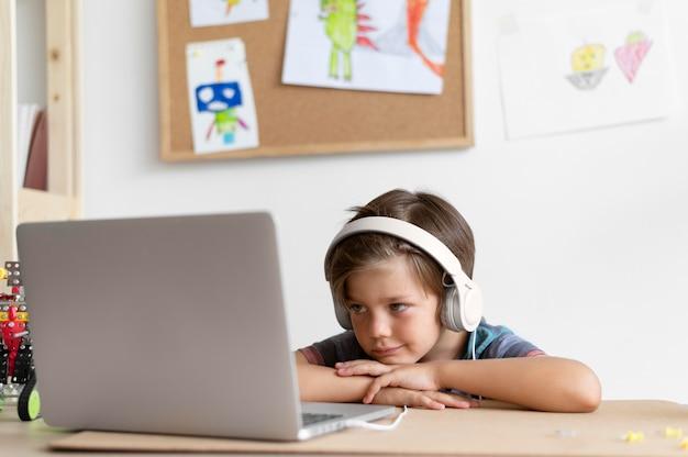 Ragazzo di tiro medio seduto alla scrivania con il laptop