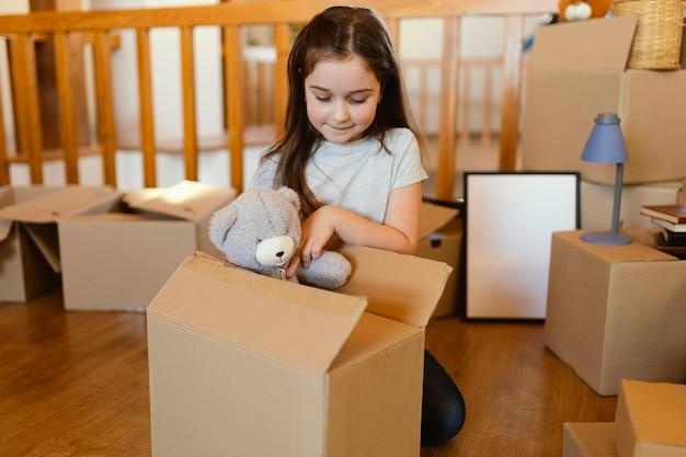 おもちゃで床に座っているミディアムショットの子供