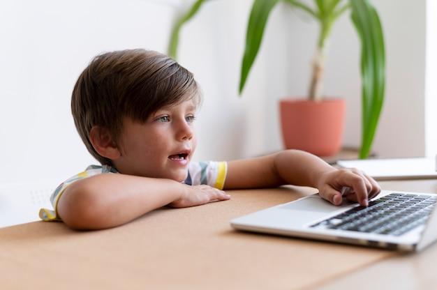 Medium shot kid typing on keyboard