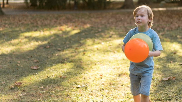 屋外で風船を持ったミディアムショットの子供