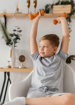 Ребенок среднего роста с гантелями на стуле