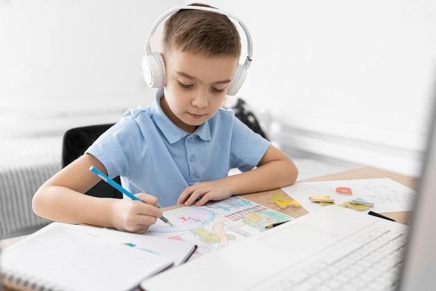 Medium shot kid with headphones drawing