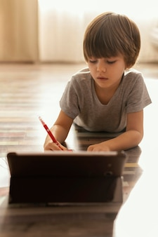Малыш среднего кадра с планшетом на полу