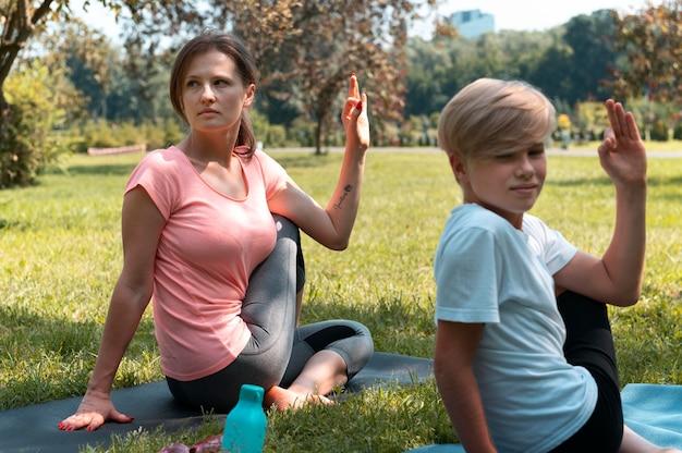 Ragazzo e donna a tiro medio sul tappetino da yoga