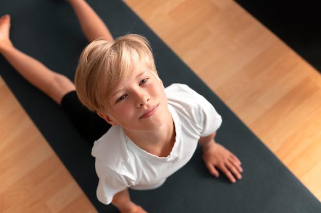 Ragazzo di tiro medio sul tappetino da yoga