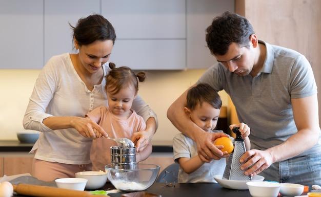 ミディアムショットの子供と親が料理をする