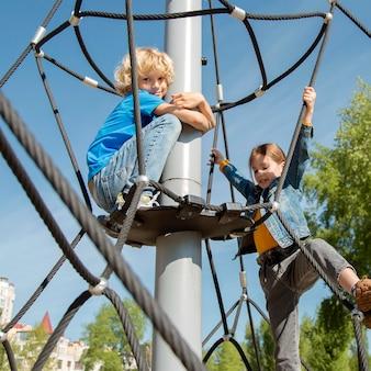 중간 샷 아이들이 함께 로프 등반