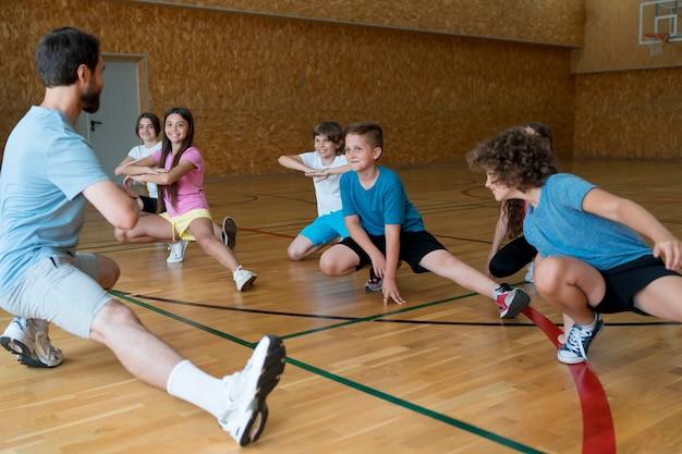 学校の体育館で運動するミディアムショットの子供たち
