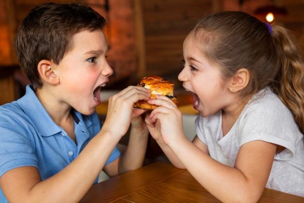 Bambini del colpo medio che tengono il dessert