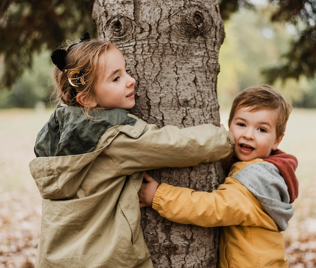 Medium shot kids hugging tree