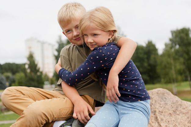 ミディアムショットの子供たちが抱き締める