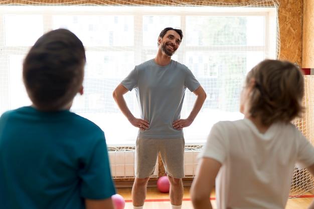 教師と一緒に学校の体育館でミディアムショットの子供たち