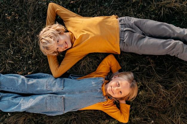 Ragazzini di tiro medio sdraiati sull'erba