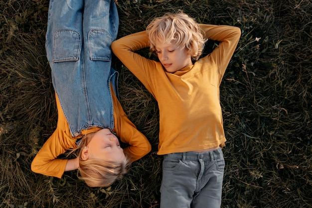 草の上に横たわるミディアムショットの子供たち