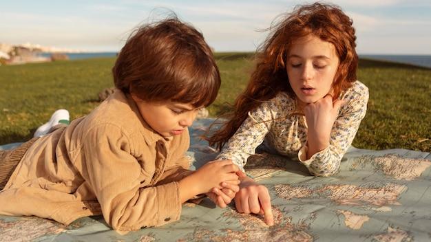 地図を見ているミディアムショットの子供たち