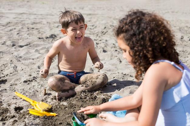 ビーチで遊ぶミディアムショットの子供たち