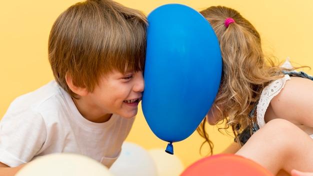 風船で遊ぶミディアムショットの子供たち
