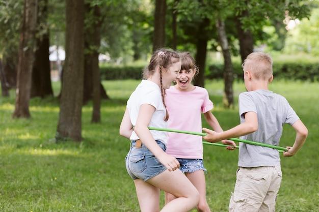 Средние выстрелы дети играют с обручем вместе