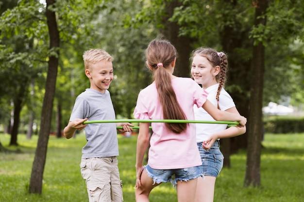 Среднего выстрела дети играют с обручем