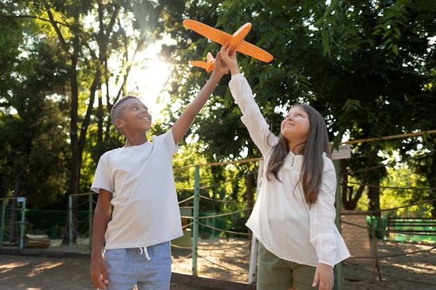 비행기를 가지고 노는 미디엄 샷 아이들