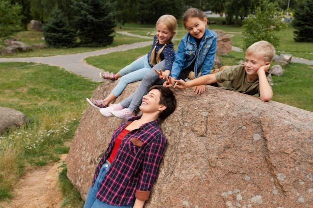 女性と遊ぶミディアムショットの子供たち